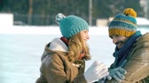 кататься на коньках : Close up of sweet young couple laughing and dusting down their clothes from snow