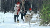 chůze : Slow motion of little girl and her father with dog on the leash approaching camera plowing through deep snow