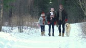 parente : Family of three walking with dog through the woods approaching camera