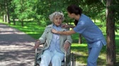 chůze : Static camera shot of female nurse talking politely to her patient in wheelchair outdoors