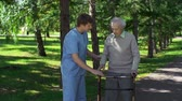assistance : Close up of medical worker instructing senior patient to use walker correctly