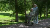 nemoc : Aged woman passing by camera pushing her friend's wheelchair