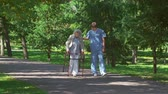 assistance : Elderly lady with walker and young caregiver approaching camera