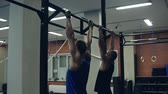 gym : Two guys doing chin-ups on fixed bar in gym Stock Footage
