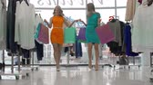 despreocupado : Tilt down the ladies with shopping bags strolling along clothes store in slow motion