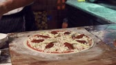 avental : Mid-section of cropped pizzaiolo adding sun dried tomatoes and mushrooms to his vegetarian pizza