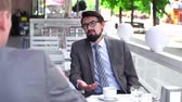 assentado : Close up of businessman chatting with his colleague seated with his back to the camera in a sidewalk cafe