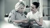 zdravotní sestra : Monochrome shot of young girl helping senior woman use the touchpad