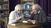 lesung : Close up of senior Paar mit einem Buch in der Bibliothek Stock Footage