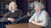 prezent : Close up of senior man singing to guitar for his sweetheart