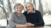 randka : Close up of jolly senior couple sitting at the table and holding hands