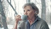 meditativo : Side view of senior lady having tea and pondering Stock Footage