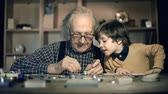 watching : Slow motion of clock master at work, his little grandson watching him mending mechanism