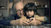 деталь : Close up of senior man with grandson repairing watch