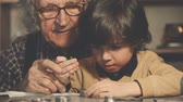 ferramentas : Close up of little boy busy screwing wristwatch parts trained by his grandfather