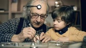 деталь : Watchmaker mending watch, his grandchild watching his work