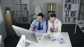 diagram : High angle view of two men at the desk making analytical research Stock Footage