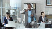 galhofeiro : Close up of Afro-American businessman standing in the middle of the office and dancing while his colleagues proceed to work ignoring him Vídeos