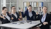 сумасшедший : Close up of four young colleagues performing exhilarated dance sitting at the office desk