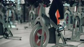 ginásio : Tilt up the unrecognizable girl doing cardio on gym cycling machine