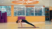 instrutor : Side view of woman doing inversion sequence at the gym