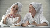 roupão de banho : Close up of girls in bathrobe with head wrapped in towel having tea