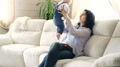 despreocupado : Side view of woman sitting on the sofa with her adorable child