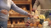 женат : Cropped unrecognizable couple choosing bread in a shop