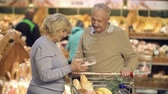 velho : Close up of mature couple choosing a cake and putting it into the trolley
