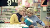 egészségügyi : Close up of two women picking toilet paper and putting it into shopping cart