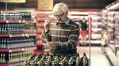 careca : Close up of adult man choosing a bottle of brandy at the supermarket