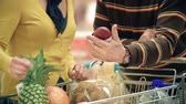 mão humana : Cropped unrecognizable couple putting shower gel in the shopping trolley