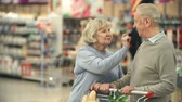 müşteri : Close up of elderly couple standing in the supermarket talking Stok Video