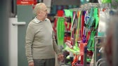 careca : Front view of elderly man approaching camera choosing a mop in the supermarket