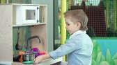 meble : Boy finishing playing with mini kitchen