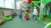 três : Tracking shot of three kids approaching camera running through the huge playroom
