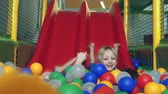 despreocupado : Close up of two kids sliding from the sliding board to the ball pit