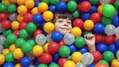 diversão : Direct from above view of little boy lying in the ball pit covered by multicolored hollow balls