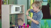 meble : Side view of little boy cooking in play kitchen set