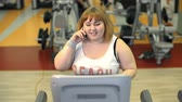 ginásio : Front view of stout lady running on gym equipment and talking on the phone