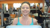 культурист : Front view of fit lady cardio training and listening to music in a gym