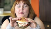 posiłek : Close up of overweight woman eating a hamburger