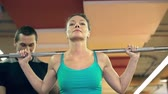 heavy : Close up of woman doing barbell back squat backed up by her personal instructor Stock Footage