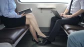 нога : Mid-section of man and woman seated in train facing each other and busy reading and laptop working Стоковые видеозаписи