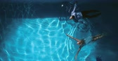 desgaste : High angle view of couple in evening wear swimming across pool