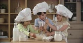 farinha : Three adorable little cooks stirring dough together