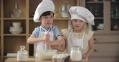 farinha : Lovely little boy and girl making dough in domestic kitchen Stock Footage