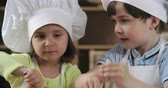 farinha : Two cute kids mixing thoroughly ingredients for batter