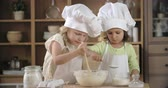 farinha : Two lovely little girls making pastry dough of flour, eggs, and sugar Stock Footage