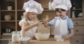 avental : Little bakers adding sugar to batter and mixing it